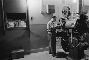 800px-Man_working_with_a_projector_in_a_movie_theater_1958